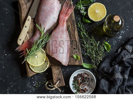 Fresh raw ruby snapper herbs and spices on a dark background. Cooking dinner