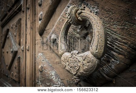 A large decorative vintage door handle on a wooden door