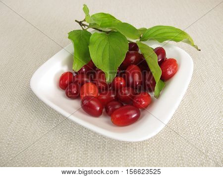 Ripe cornelian cherries with leaves in bowl