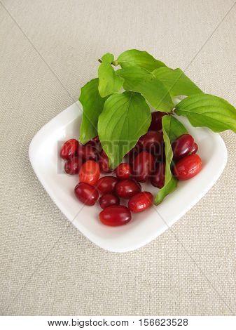 Ripe cornelian cherries with leaves in bowl