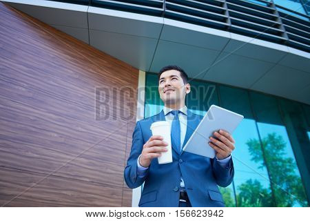 Confident businessman with digital tablet and disposable cup standing near office building and waiting for colleague