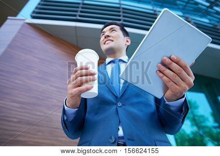 Asian young man holding disposable cup and digital tablet