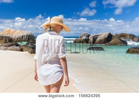 Woman wearing white loose tunic over bikini and beach hat on Mahe Island, Seychelles. Summer vacations on picture perfect tropical beach concept.