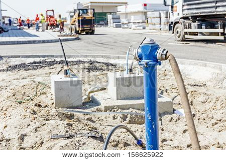 Water hose is attached to newly placed fire hydrant on construction site.