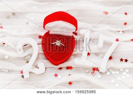 New Year 2017 on white fabric background with engagement diamond ring in red gift box. Good for Valentine's day and Happy New Year cards. top view flat lay. Place for text.