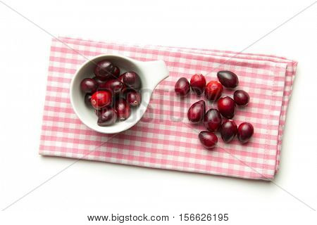 The tasty american cranberries in bowl on checkered napkin.
