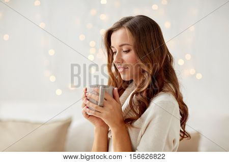 morning, leisure, christmas, winter and people concept - happy young woman with cup of coffee or tea at home