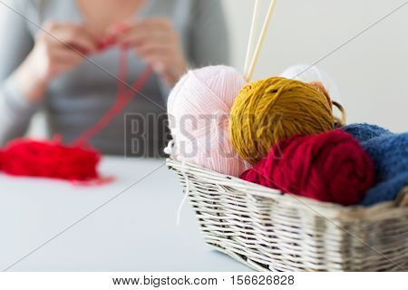 people and needlework concept - wicker basket with knitting needles and balls of yarn over woman