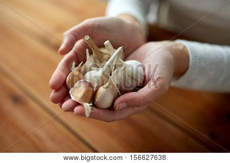 health, people, food, traditional medicine and ethnoscience concept - woman hands holding garlic for cooking or healing