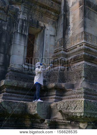 Caretaker cleaning at Phimai historical park. Prasat Hin Phimai Nakhon ratchasima Thailand.