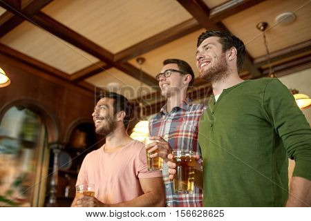people, leisure, friendship and sport concept - happy male friends watching sport game or football match and drinking beer at bar or pub
