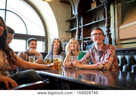 people, leisure, friendship and entertainment concept - happy friends drinking beer and watching sport game or football match at bar or pub