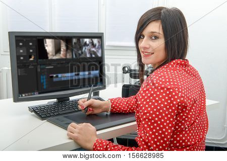 young brunette female designer using graphics tablet for video editing