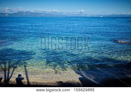 Ionian sea. shadow of man and trees on water