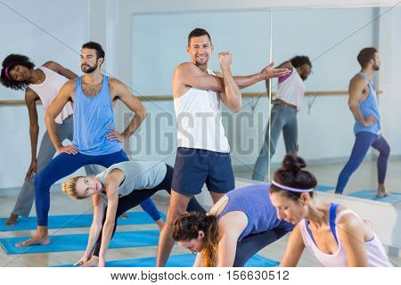 Group of people performing stretching exercise in gym