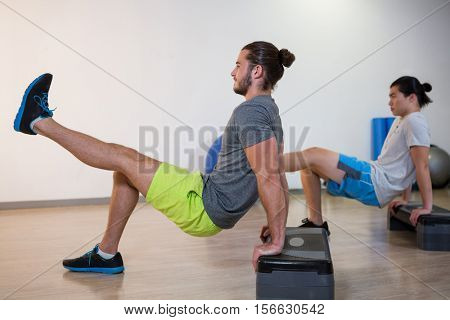 Two men doing aerobic exercise on stepper in fitness studio