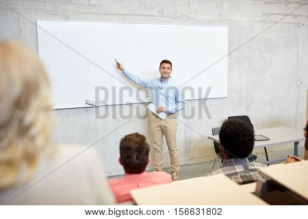 education, high school, university, teaching and people concept - group of international students and teacher with marker standing at white board at lecture