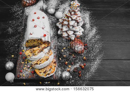 Christmas stollen. Traditional German European festive dessert. Ingredients cranberries pine nuts for Christmas Stollen. Stollen cake cut into pieces. Christmas food card. Christmas gingerbread fir tree. Dark Black background