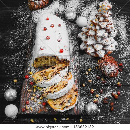Christmas food card. Traditional Christmas stollen German festive dessert. Ingredients cranberries pine nuts for Christmas Stollen. Christmas gingerbread fir tree. Stollen cake cut. Black background
