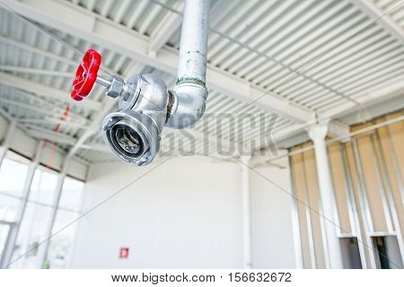Red faucet from firefighter galvanized steel pipeline is hanging from ceiling.