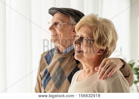 Mature man and woman looking through a window