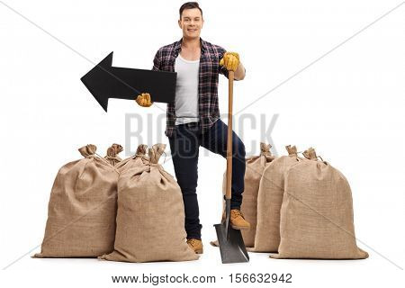 Full length portrait of a farmer standing between burlap sacks with a shovel and an arrow pointing left isolated on white background