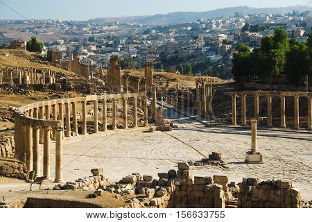 Photo of the Oval Forum and long colonnaded street or cardo ancient Greco-Roman city Gerasa. Modern Jerash on background. Tourism industry, tourist attraction, travel concept.