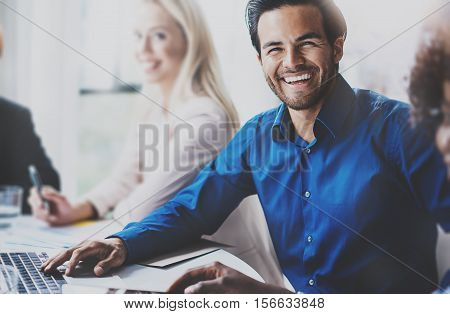 Portrait of successful hispanic businessman smiling on the business meeting with partners in modern office.Horizontal, blurred background