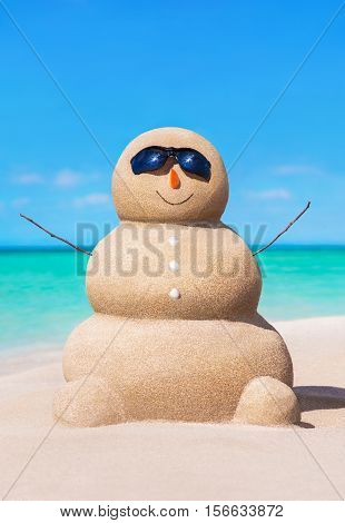Funny sandy snowman with carrot nose at tropical ocean beach. Holiday concept for New Year and Christmas travel destinations to hot coastal countries.