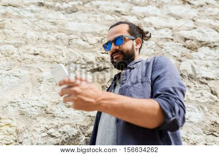 leisure, technology, communication and people concept - man in sunglasses texting message on smartphone at stone wall