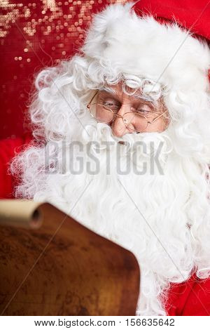 Portrait of happy Santa Claus holding Christmas letter .