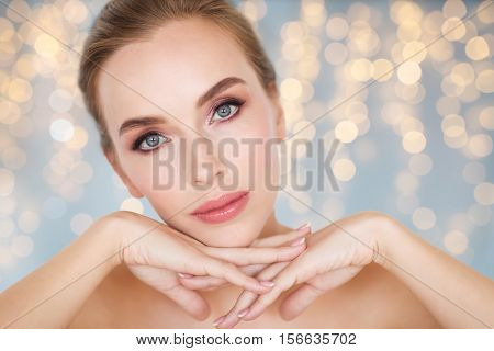beauty, people, holidays and skin care concept - beautiful young woman face and hands over lights background