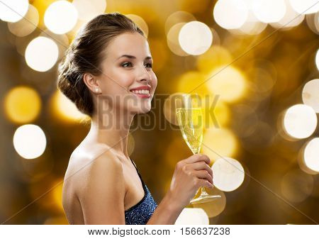 party, drinks, holidays, luxury and celebration concept - smiling woman in evening dress with glass of champagne over lights background