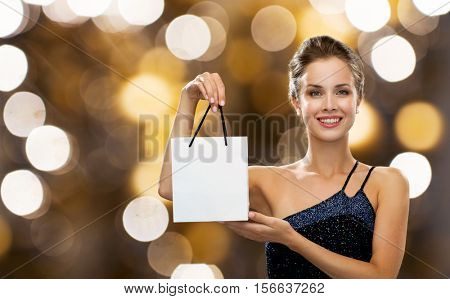luxury, advertisement, holydays, people and sale concept - smiling woman with white blank shopping bag over lights background