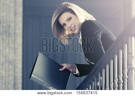 Happy young business woman with a folder at the office building. Female fashion model outdoor