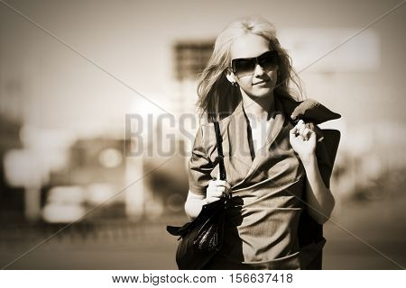 Blond business woman in sunglasses walking on city street. Stylish fashion model outdoor