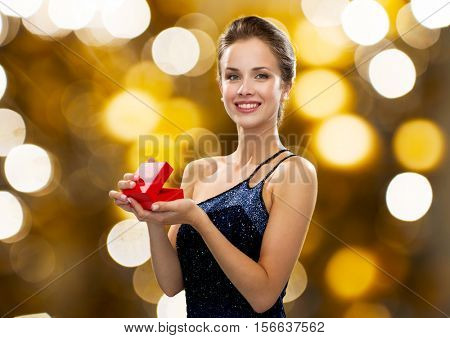 holidays, presents, luxury and people concept - smiling woman in dress holding red gift box over lights background
