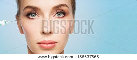 people, cosmetology, plastic surgery, anti-aging and beauty concept - beautiful young woman face and syringe making injection to eye area over blue background