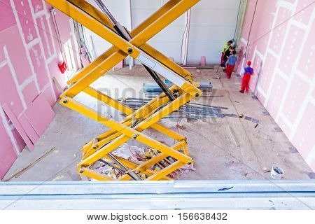 Scissor lift platform with stretched hydraulic system at maximum height range.