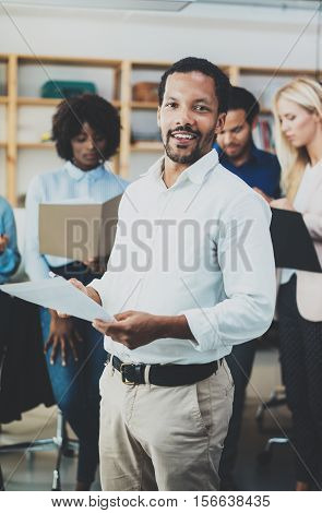 Teamwork concept in modern office.Young african businessman wearing white shirt holding papers at hands and standing front of the coworkers team.Vertical, blurred background poster