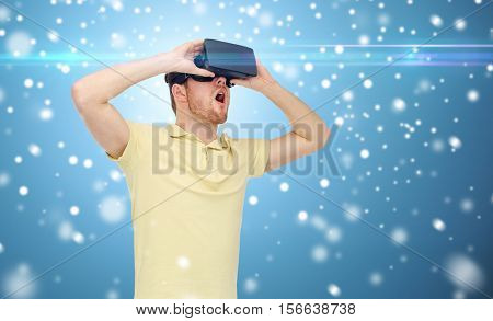 technology, augmented reality, winter, christmas and people concept - happy young man with virtual headset or 3d glasses playing game over snow on blue background and laser light