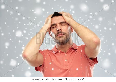 people, crisis, winter, christmas and stress concept - unhappy man suffering from head ache over snow on gray background