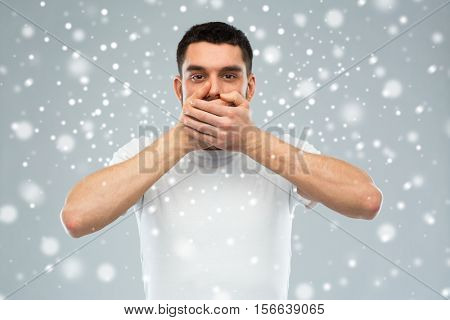 emotion, silence, winter, christmas and people concept - man in white t-shirt covering his mouth with hands over snow on gray background