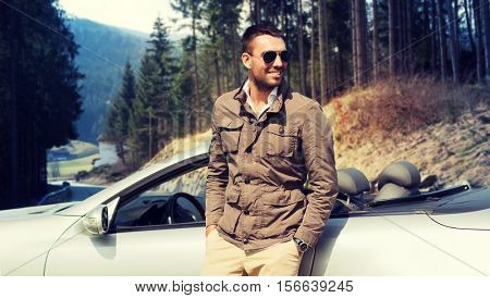 travel, tourism, road trip, transport and people concept - happy man near cabriolet car over natural background
