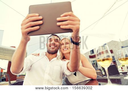 love, date, technology, people and relations concept - smiling happy couple taking selfie with tablet pc computer at restaurant terrace