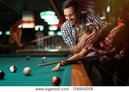 Couple playing snooker, pool and smiling together