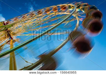 Blurry Ferris Wheel In Motion On Blue Sky Background