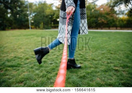 Legs of woman walking with her dog on leash on a green grass outdoors