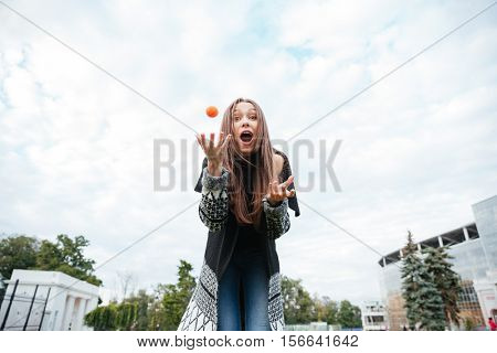 Surprised cute young woman standing and playing with dog outdoors