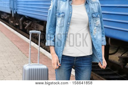Young woman in blank t-shirt standing on railway platform with suitcase, closeup